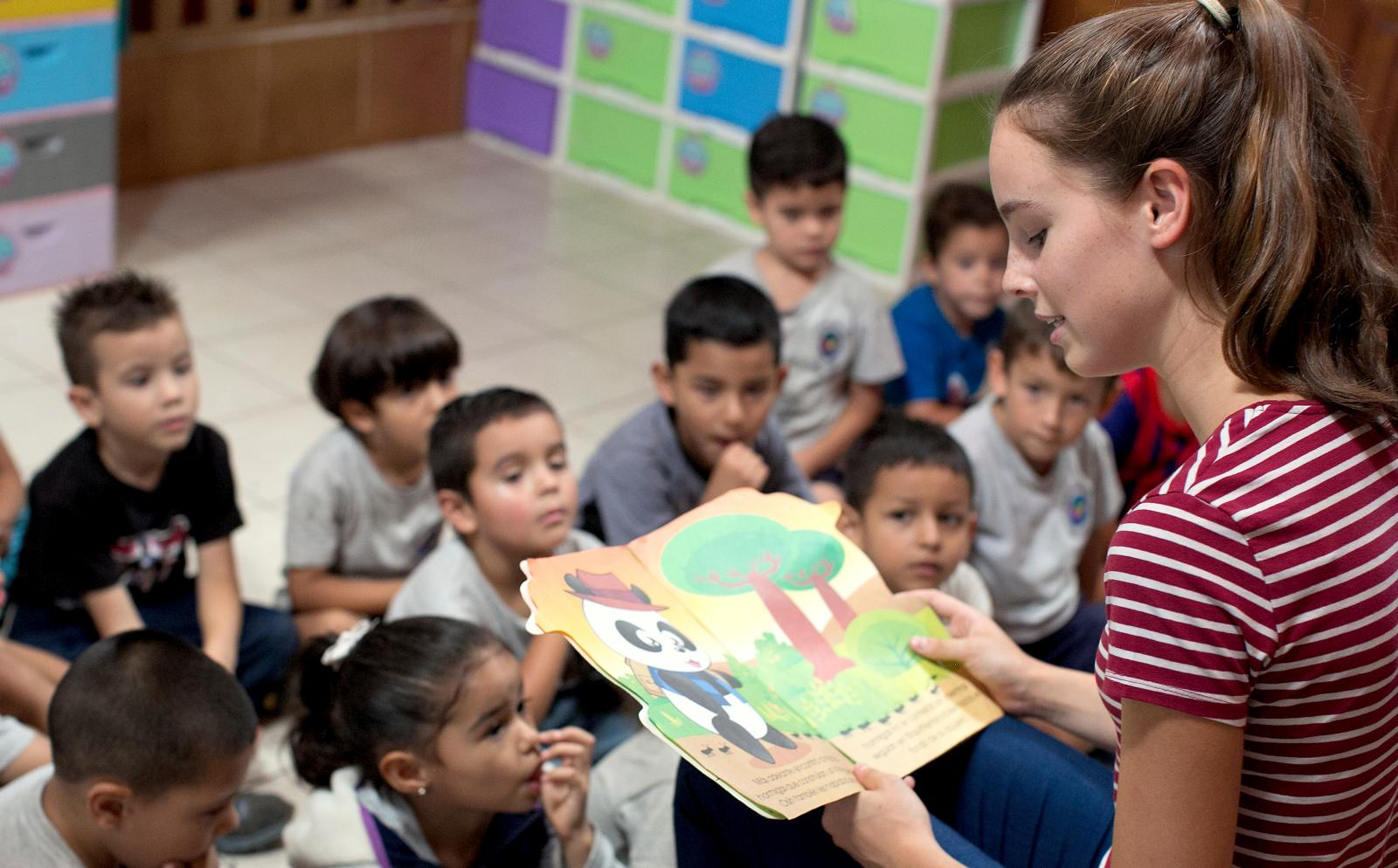 Childcare and Conservation volunteer reads a story to the children in her class